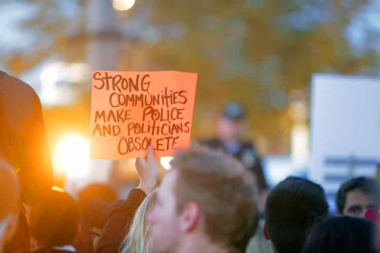 A photo of a protester with an orange placards