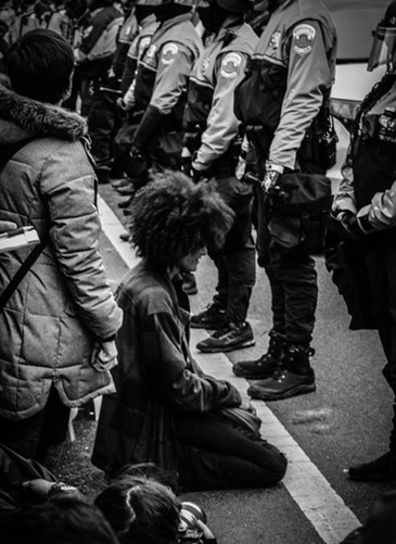 A photo of a woman kneeling in front of a group of policemen